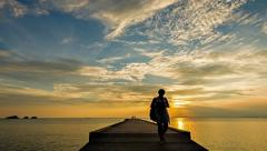 People walking on the pier at sunset on a tropical island - stock footage