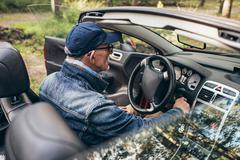 Rear view of senior man in sports car in nature. Stock Photos