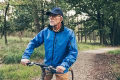 Resting senior man standing with bicycle on forest trail. Stock Photos