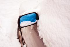 Reflection of fresh snow in automobiles mirror. - stock photo
