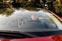 Senior man sitting in sports car outdoors in park. Stock Photos