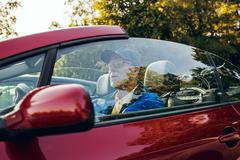 Side view of senior man sitting in sports car outdoors in park. Stock Photos