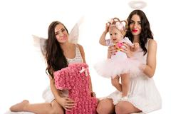 two beautiful brunette angels with little baby - stock photo