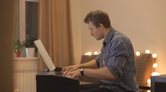 Young man playing the piano Stock Footage