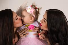 Two beautiful angels kissing little baby Stock Photos
