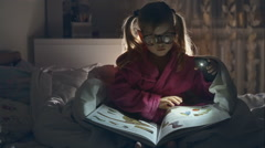 The little girl with glasses reading a book sitting in bed under the covers. Big Stock Footage