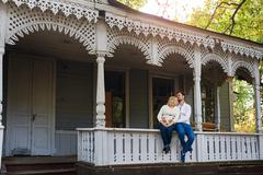 husband with his pregnant wife on the porch of the house - stock photo