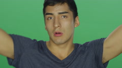 Young man dances and makes funny faces, on a green screen background Stock Footage