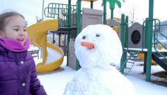 Little girl making a snowman - stock footage