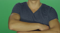 Young man crosses his arms in anger, on a green screen background - stock footage