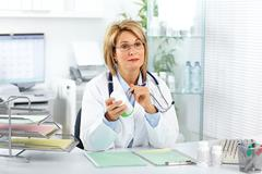 Mature doctor woman with pills. - stock photo