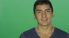 Young man with black hair smiling, on a green screen background - stock footage