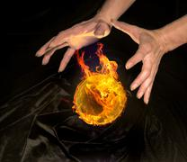 Burning crystal ball and hands Stock Photos