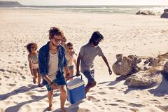 Group of friends carrying cooler to party on beach - stock photo