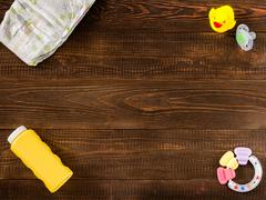 disposable diaper, teether, dummy, baby powder and rubber duckling on dark wo - stock photo