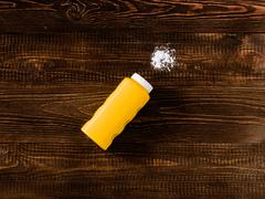 Spilled baby talcum powder on dark wooden background. Flat lay Stock Photos