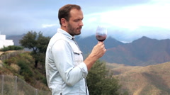 Young pensive man standing with wine in the country mountains, 240fps Stock Footage