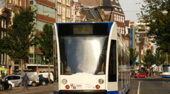 Zoom Out of Trams Passing on Busy Street in Amsterdam Netherlands Stock Footage