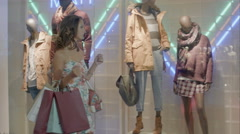 Woman in shopping center with bags. Fashion girl in mall looking on shopwindow - stock footage