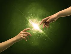 Stock Photo of Touching arms lighting spark at fingertip
