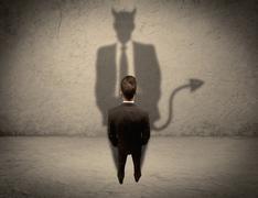 Salesman facing his own devil shadow Stock Photos