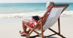 Retired old man using tablet while lying on deckchair Stock Footage