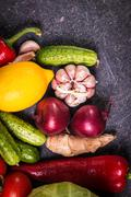 Assortment of fresh vegetables close up on black table - stock photo