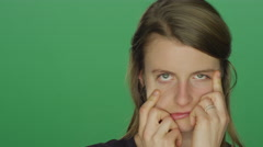 woman makes funny faces, on a green screen background - stock footage