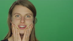Woman makes funny faces and smiles, on a green screen background Stock Footage