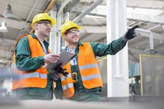 Workers in protective workwear talking with clipboard in factory Stock Photos