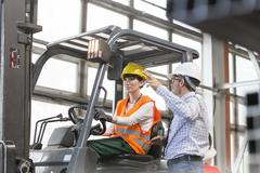 Supervisor directing worker driving forklift in factory Stock Photos