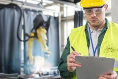 Worker in protective workwear with clipboard in factory - stock photo