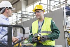Engineer and worker in protective workwear talking in factory - stock photo