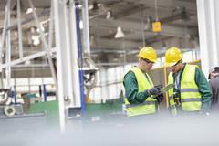 Workers in protective workwear talking with clipboard working in factory - stock photo