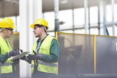 Workers in protective workwear talking with clipboard - stock photo
