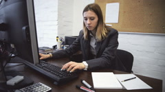 Portrait business woman at desk typing on computer - stock footage