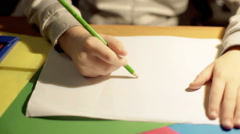 Stock Video Footage of Child painting something on papers using green crayon