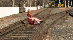 Blond Woman Sitting On Rail Road Tracks Red Dress Stock Footage