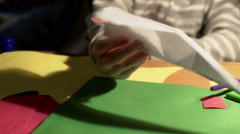 Child showing a plane made of paper while sitting at the table Stock Footage