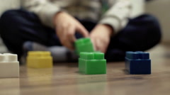 Child sitting on the floor and playing with colorful blocks Stock Footage