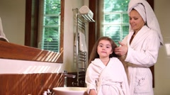 Mother combing hair of her little daughter - stock footage
