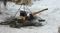 Soldier cooks porridge on the fire and drops to the ground spoon Stock Footage