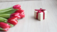 Red-white tulips and gift box with bow on white table Stock Footage