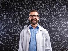 Teacher in white coat  and eyeglasses against big blackboard wit - stock photo