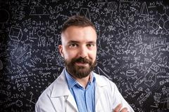 Teacher in white coat against big blackboard with mathematical s - stock photo