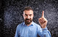 Scolding teacher against big blackboard with mathematical symbol - stock photo