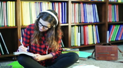 Girl writing, listening music and smiling to the camera in the library Stock Footage