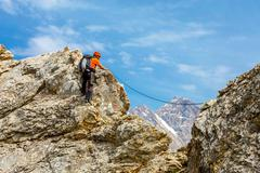 Brave man climbs rocky ridge Stock Photos