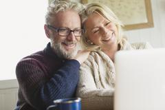 Smiling senior couple using laptop in kitchen Stock Photos