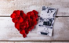 Photos of a couple in love. Red rose petal heart - stock photo